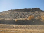 Outcrop of the Niobrara Formation near Wagon Mound, NM. Seven prominent limestone beds halfway up the slope are locally mapped as the Fort Hays Limestone; compare these to the thick limestones in the previous picture. The outcrop is capped by Quaternary basalt; a halo of contact metamorphism is visible just below the basalt.